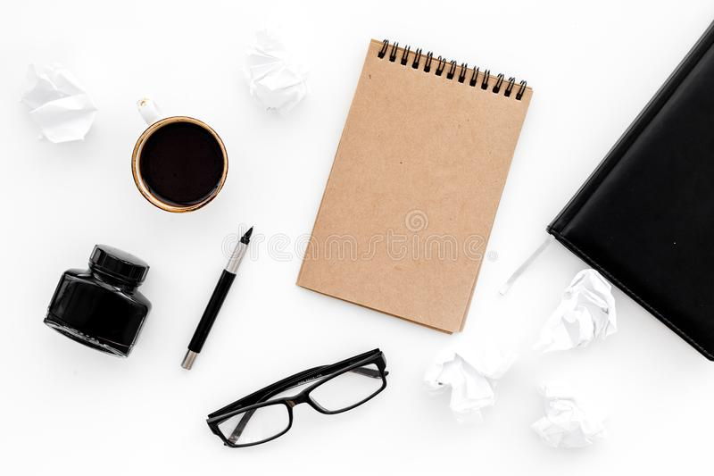 Ink, dip pen, notebook, coffee, glasses for writer workplace set on white office background top view mock-up royalty free stock photography