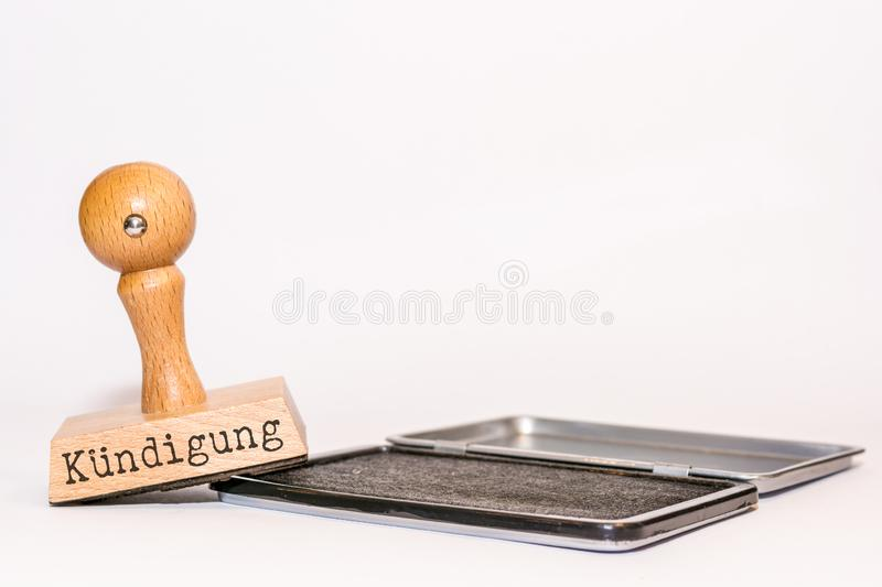 Ink pad and stamp with the German word `Termination` on it in front of white background. Wooden stamp with the inscription in German for cancellation on ink pad royalty free stock photo