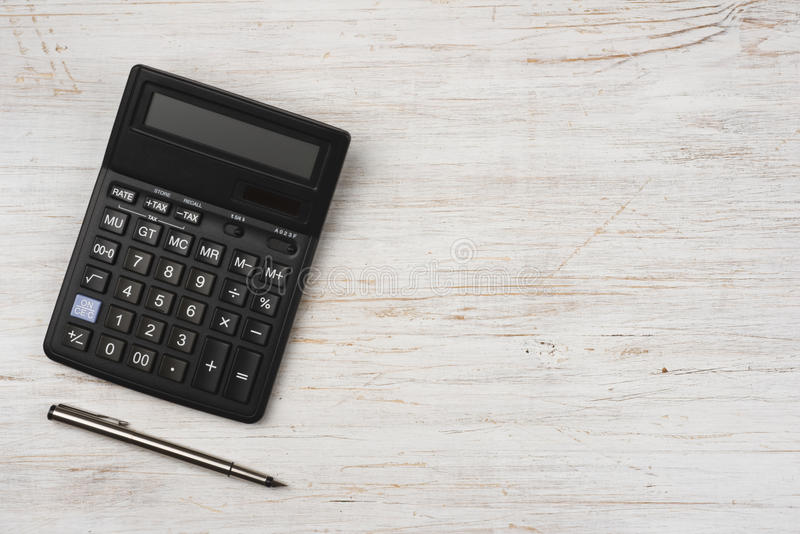 Ink pen and black calculator on wooden texture background royalty free stock photos
