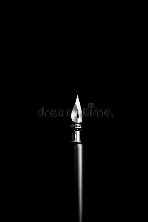 An ink pen with a metal tip close-up on a black background. classic fountain pen isolated macro black and white. copy space. stock photo