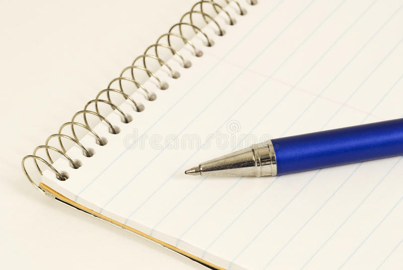 Ink Pen on Steno Pad. A blue ink pen laying on a spiral steno pad royalty free stock image