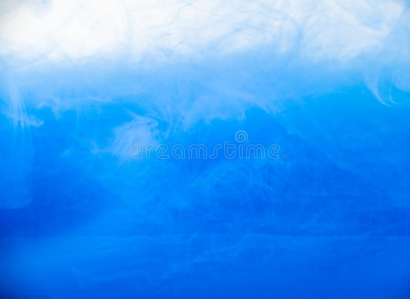 Ink in water, close up. Abstract background. Blue paint dissolving into water. Abstract acrylic clouds in liquid. Waves. Of acrylic ink in water. Abstract royalty free stock photos