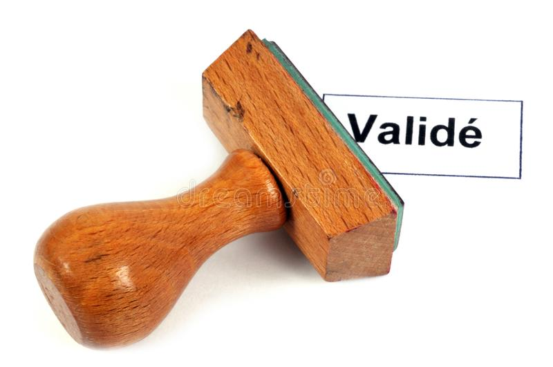 Inking stamp indicating validated. Validated French word written with an inkpad in close-up and on a white background stock illustration