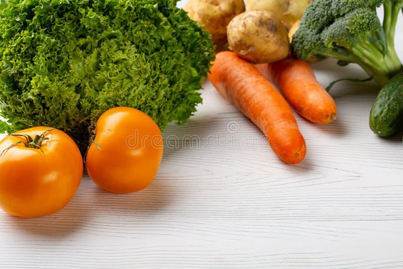 Inkludera nya organiska grönsaker på det vita trägolvet med kopieringsutrymme royaltyfria bilder