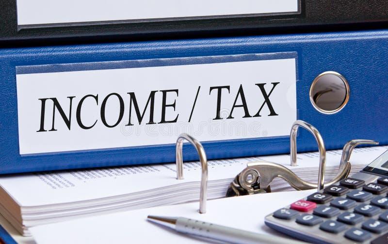 Inkomst och skatt - blå limbindning med text i kontoret arkivbild