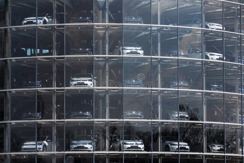 Inkopplingshybrid- Volkswagen e-golf elbilar står bak exponeringsglas i Glasernen Manufaktur - den genomskinliga fabriken, Dresde arkivfoto
