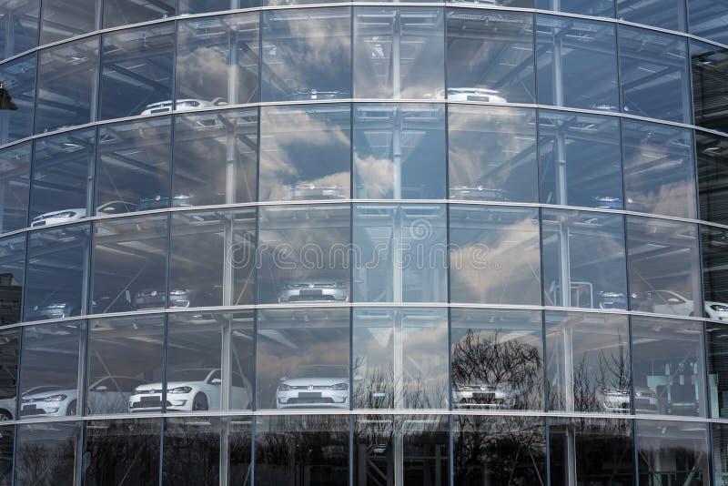 Inkopplingshybrid- Volkswagen e-golf elbilar står bak exponeringsglas i Glasernen Manufaktur - den genomskinliga fabriken, Dresde arkivbild