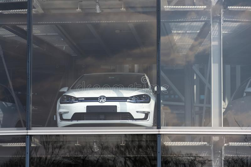 Inkopplingshybrid- Volkswagen e-golf elbilar står bak exponeringsglas i Glasernen Manufaktur - den genomskinliga fabriken, Dresde royaltyfri foto