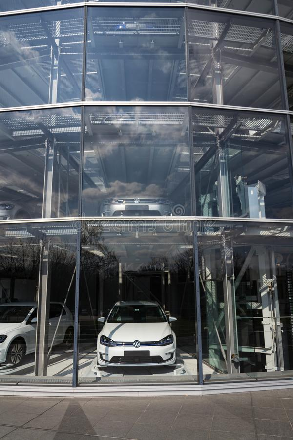 Inkopplingshybrid- Volkswagen e-golf elbilar står bak exponeringsglas i Glasernen Manufaktur - den genomskinliga fabriken, Dresde royaltyfri bild