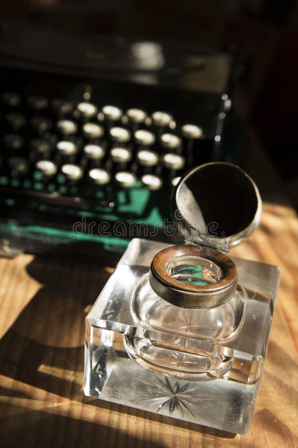 Inkwell and a typewriter. Antique crystal inkwell and a typewriter royalty free stock image