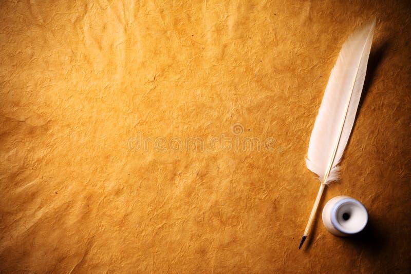 Inkwell y pluma en un papel viejo fotografía de archivo libre de regalías