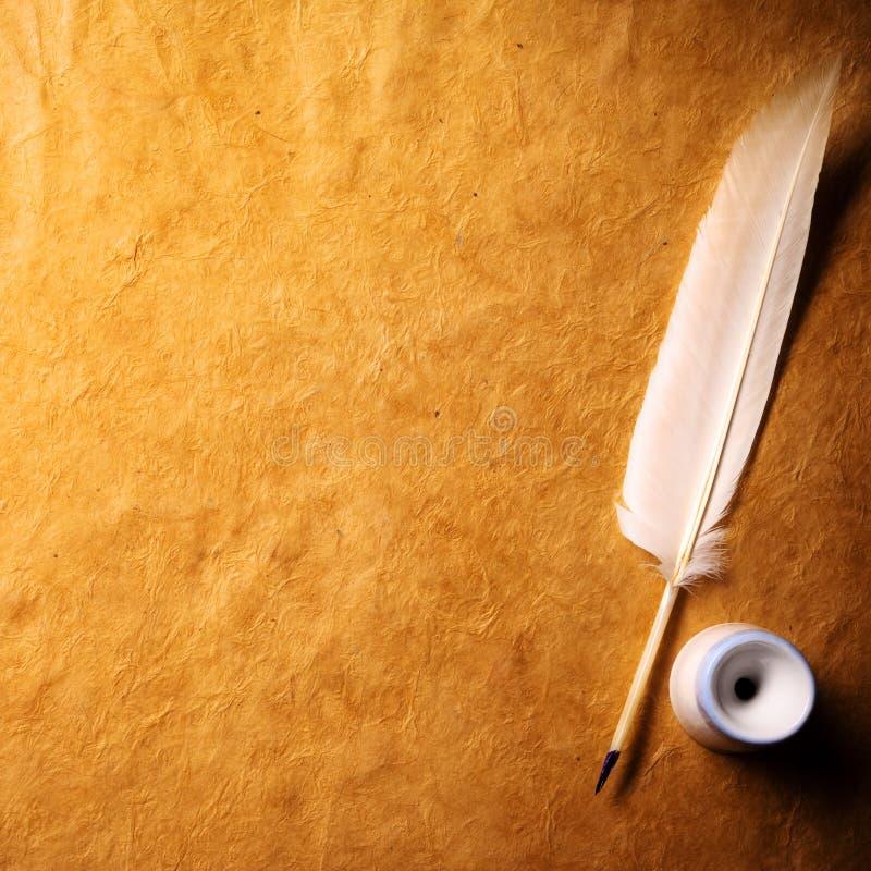 Inkwell y pluma en un papel viejo foto de archivo
