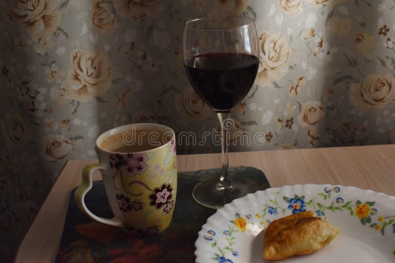 Inländischer Wein im Glas mit einer halb aufgegessenen Torte lizenzfreies stockbild