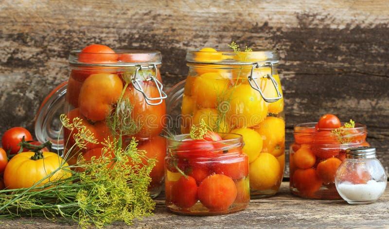 Inlagd tomat i krus på trätabellen Tomater jäst processexponeringsglas skorrar variation - röd guling, apelsinfärger arkivfoto