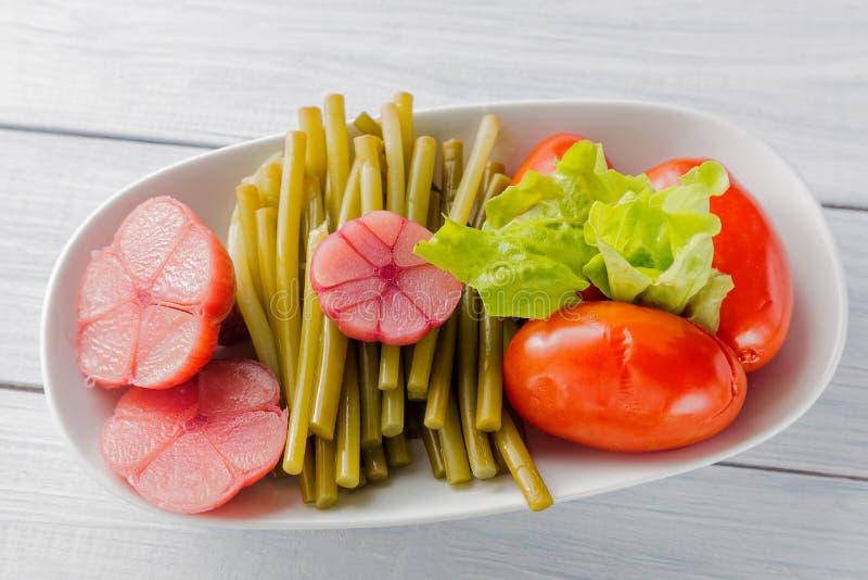 Inlagda grönsaker stänger sig upp Vitlök, lös purjolök och tomat på den vita plattan och trätabellen Top beskådar arkivfoton