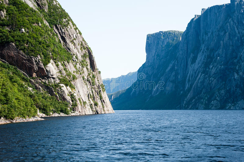 Inland fjord between large steep cliffs. With some green vegetation on rock face, at Western Brook Pond, Gros Morne National Park, Newfoundland, Canada royalty free stock photos