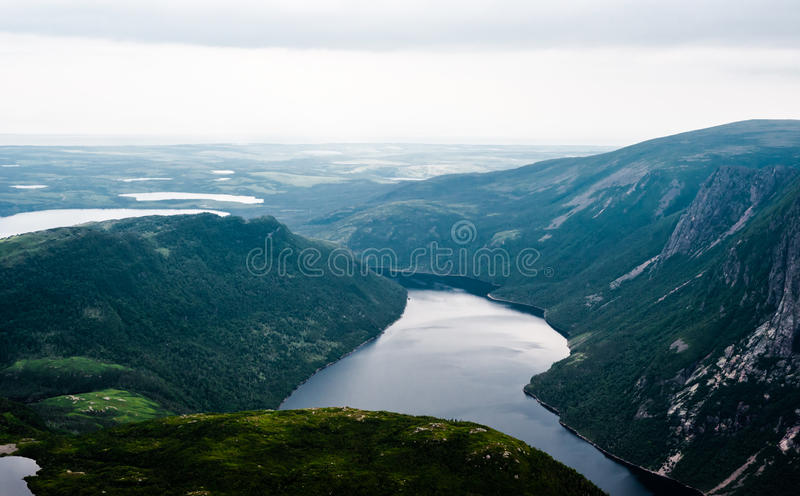 Inland fjord between steep cliffs against green landscape royalty free stock images