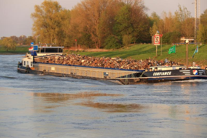 Inland shipping cargo ship with scrap metal. Inland shipping on the river ijssel near the dutch city velp. Ship with scrap metal as cargo. Boat with dutch flag royalty free stock photography