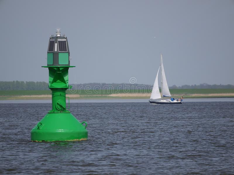 Inland shipping regulation Green light buoy with solar panels as energy source , Blurred, background. River elbe germany stock photography