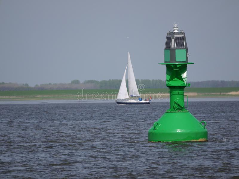 Inland shipping regulation Green light buoy with solar panels as energy source , Blurred, background with sailboat. River Elbe near Hamburg Germany stock images