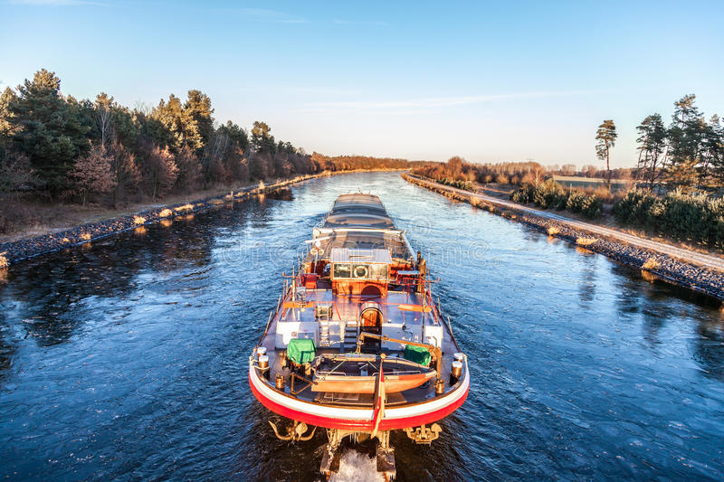Inland vessel drives a canal. River along stock photo