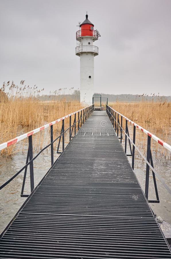 Inland waterway lighthouse seen from a steel pier royalty free stock images