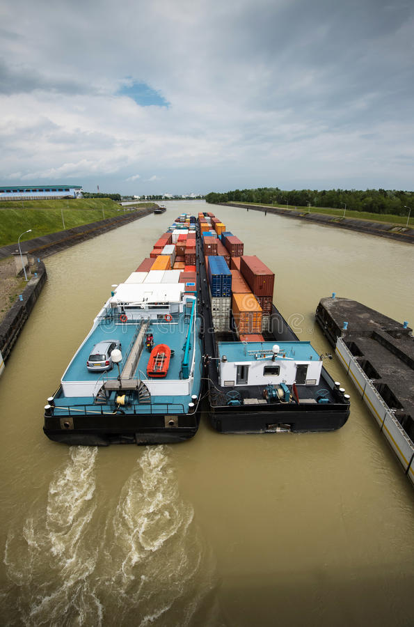 Inland waterway transportation. Containership inland waterway transportation on river at watergate royalty free stock image