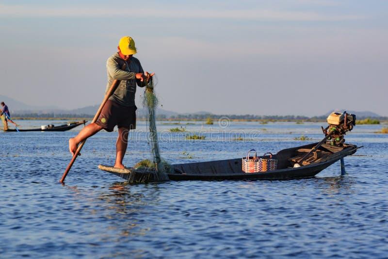 Inle湖,缅甸,2018年11月20日-工作地道的渔夫检查他们的在Inle湖水的网  免版税库存图片