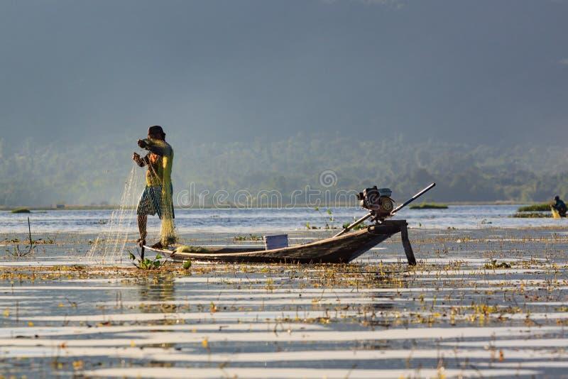 Inle湖,缅甸,2018年11月20日-工作地道的渔夫检查他们的在Inle湖水的网  免版税库存照片