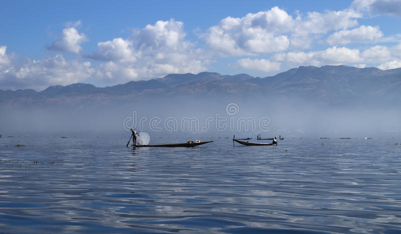 Inle lake fisher. Bright shot of a inle lake fisher with the view on the mountains, Myanmar royalty free stock photo