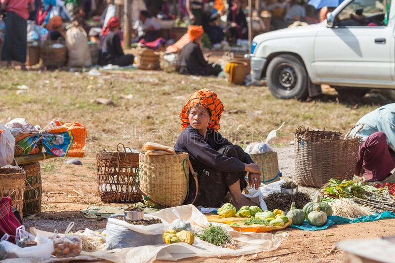 Inle Lake, Woman at the Ywama village market. Inle Lake, Myanmar-December 20, 2015. Pa`O tribe woman selling vegetables in traditional Sunday market in local stock photo
