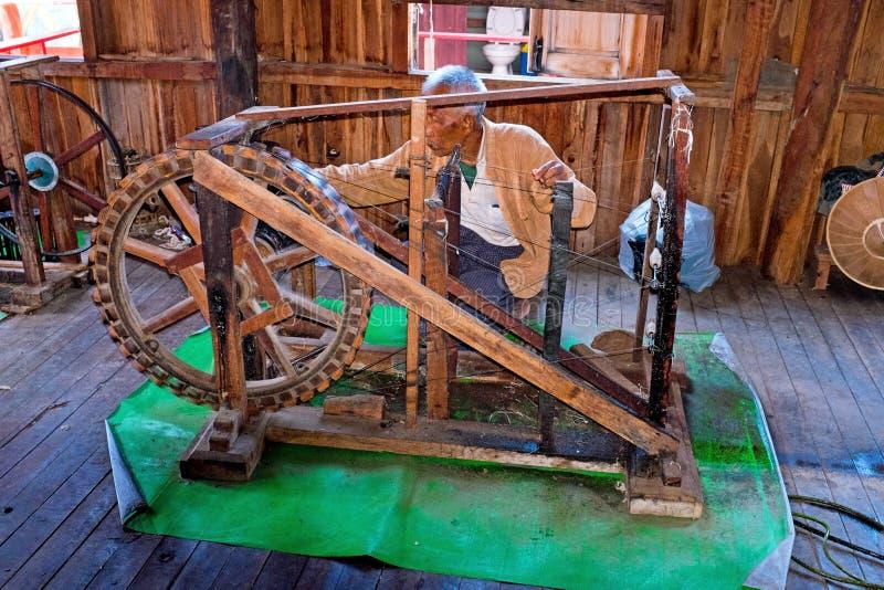 INLE LAKE, MYANMAR - NOVEMBER 22, 2015: Man behind an old fashioned loom in Burma Asia royalty free stock image