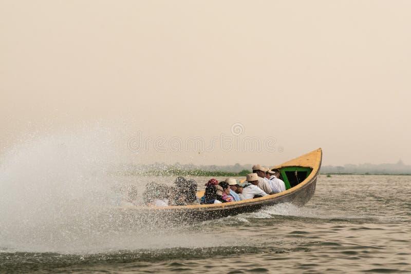 Inle, Myanmar - April 2019: Burmese people having boat ride on Inle lake. In traditional long boats, burma, tourist, holidays, transport, water, transportation royalty free stock image
