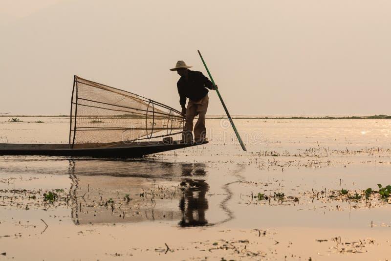 Inle, Myanmar - Maart 2019: Traditionele Birmaanse been roeiende visser bij Inle-meer stock afbeelding