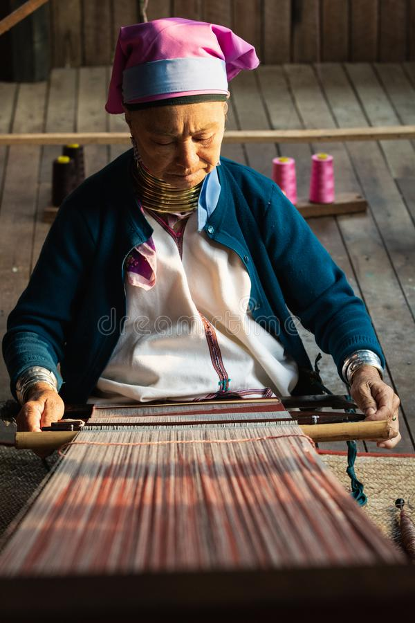 Inle, Myanmar - marzo de 2019: La mujer larga del cuello de la tribu de Kayan Lahwi se sienta detrás del telar fotos de archivo libres de regalías