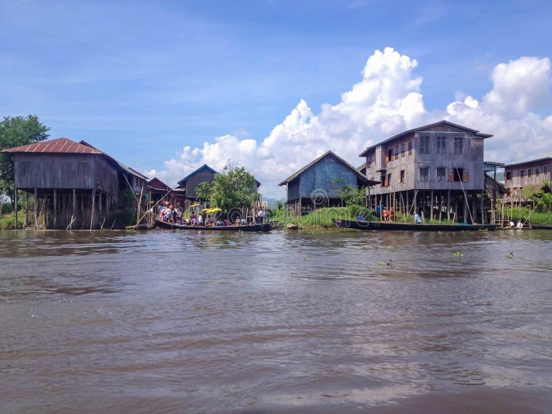 INLE-SEE, MYANMAR - 26. MAI 2014: Lokale Leute sind auf longtail Boot vor sich hin- und herbewegendem Dorf am Inle See lizenzfreie stockbilder