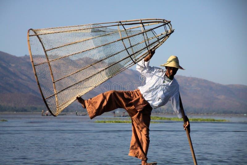 INLE-SJÖ, MYANMAR - DECEMBER 23 2015: Fiskare som balanserar på ett fartyg med fiskkorgen fotografering för bildbyråer