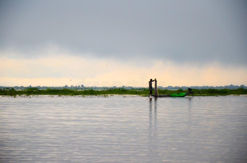 INLE-SJÖ, MYANMAR SEPTEMBER 20, 2016: Konturer av lokalt fiskarefiske för mat på soluppgång royaltyfri foto