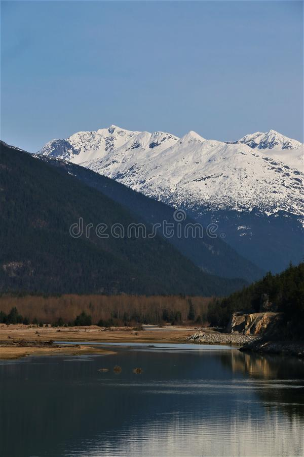 Inlet to Dyea, Alaska with snow covered mountains. Inlet to Dyea, Alaska, where historic Yukon gold rush Chilkoot Trail begins. March 2019 stock image