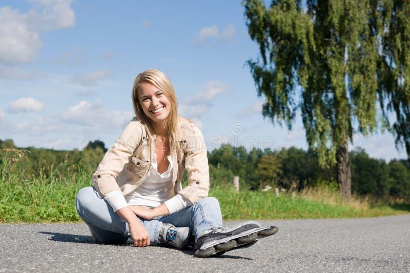 Inline skates young woman sitting asphalt road. Inline skates young attractive woman wearing jeans sitting asphalt road stock photo