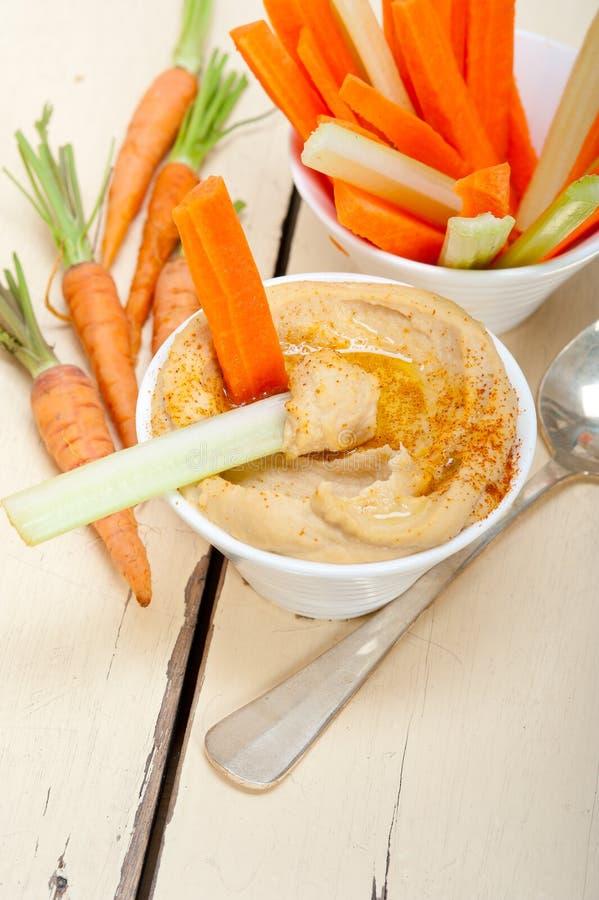 Inmersión fresca del hummus con la zanahoria y el apio crudos fotografía de archivo