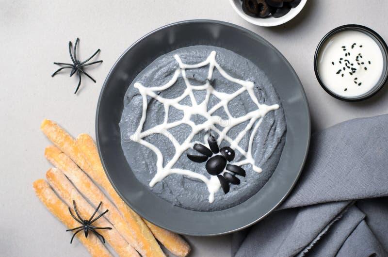 Inmersión negra de Hummus Halloween adornada con la telaraña y la araña, invitación del partido de Halloween foto de archivo