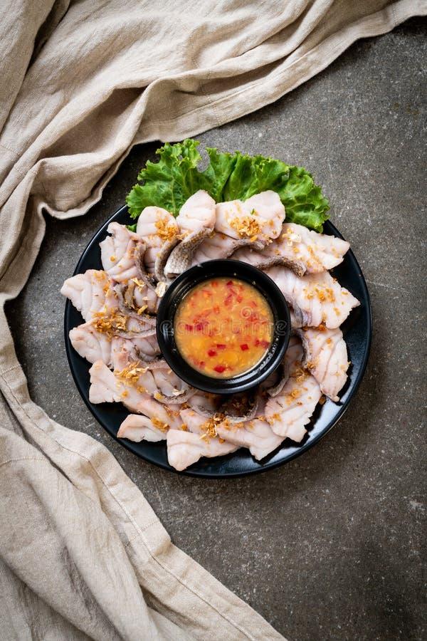 Inmersi?n hervida de los pescados con la salsa fotografía de archivo libre de regalías