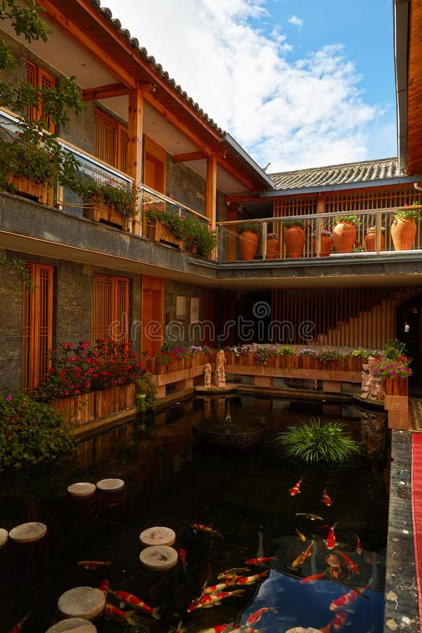 Inn with beautiful view, Lijiang, China. Listen-to-Flowers Inn with indoor view of mini pond with fishes and sky view through open wide roof. There are many royalty free stock photo