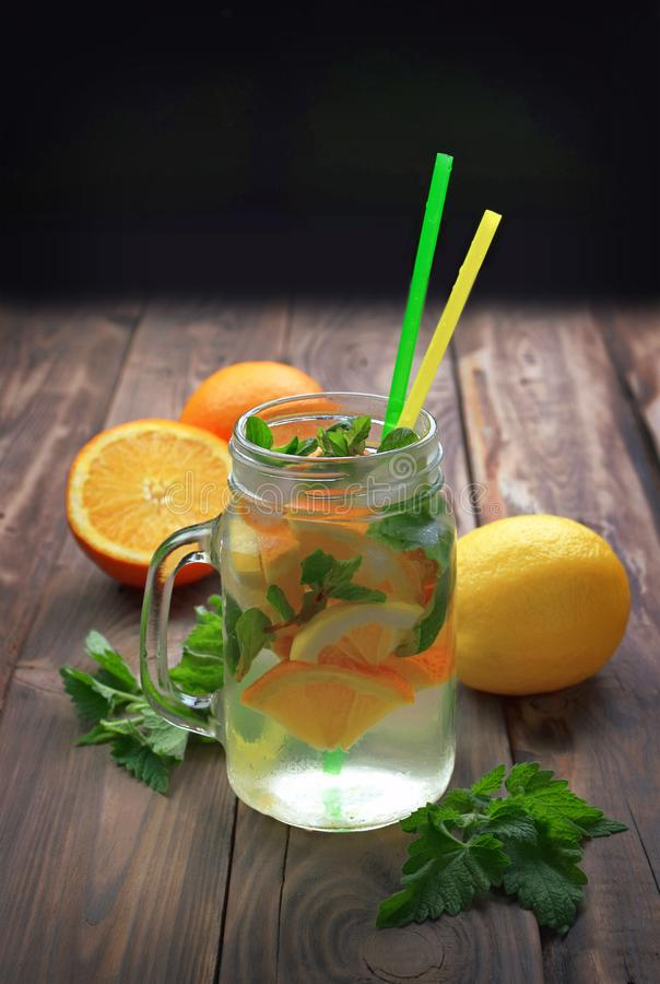 Innaffi con ghiaccio, il limone, l'arancia, la menta e la melissa Cocktail di estate immagine stock libera da diritti