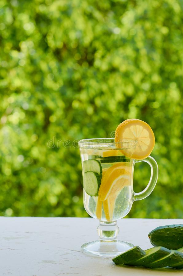 Innaffi con i limoni e le fette del cetriolo nel vetro sui precedenti vaghi della natura con lo spazio della copia Cocktail di fr immagini stock