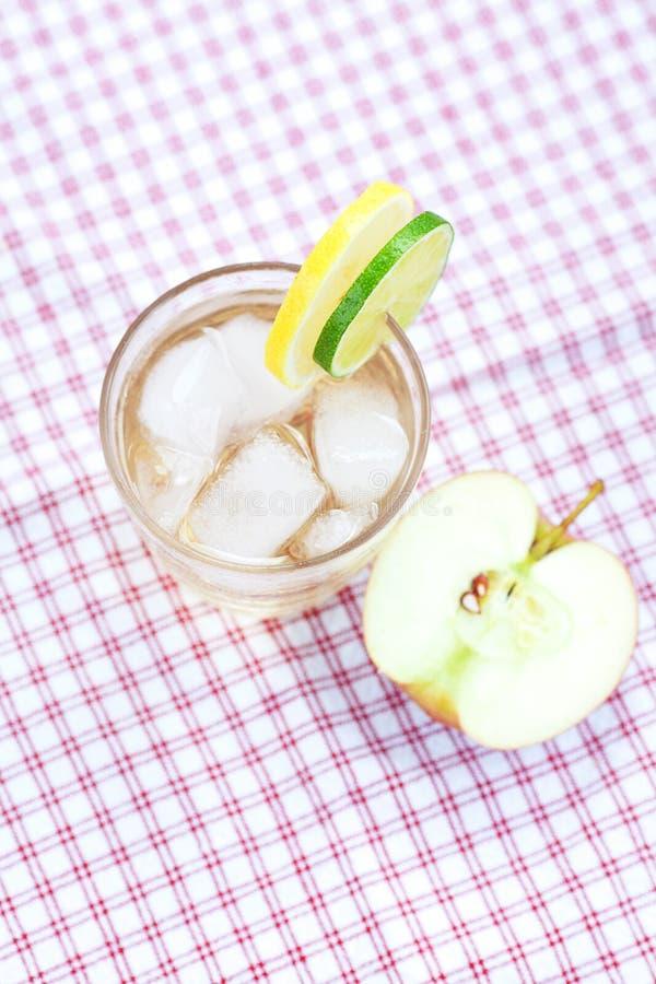 Innaffi e, mela in un vetro con ghiaccio immagini stock