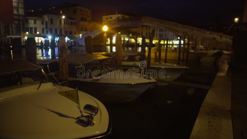 Innaffi i crogioli di taxi messi in bacino all'attracco di notte, trasporto del passeggero a Venezia immagine stock