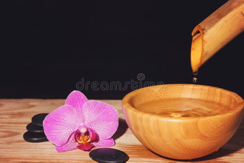 Innaffi i gocciolamenti dal bambù in una ciotola su una tavola di legno, accanto alle pietre del trattamento della stazione terma fotografie stock