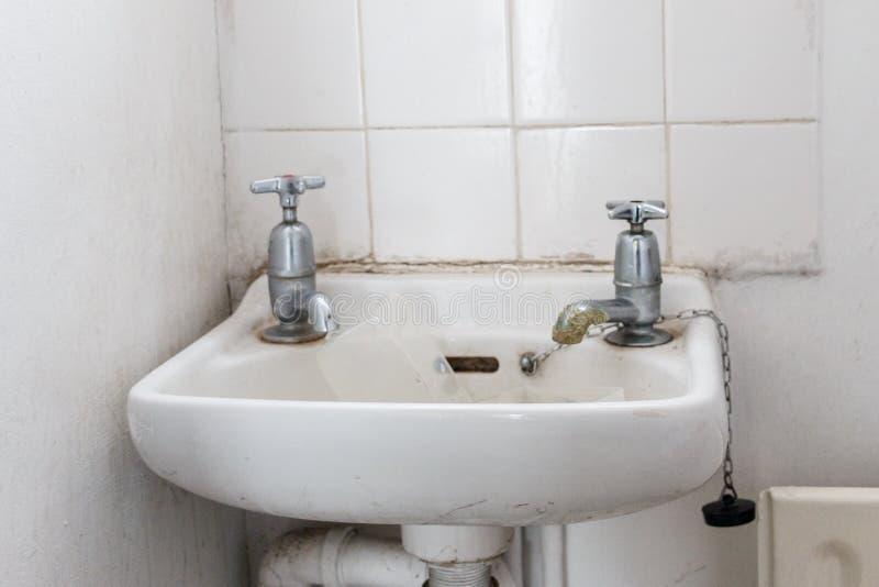 Innaffi il bacino con i rubinetti separati di acqua fredda e caldi come utilizzato in Bri immagini stock